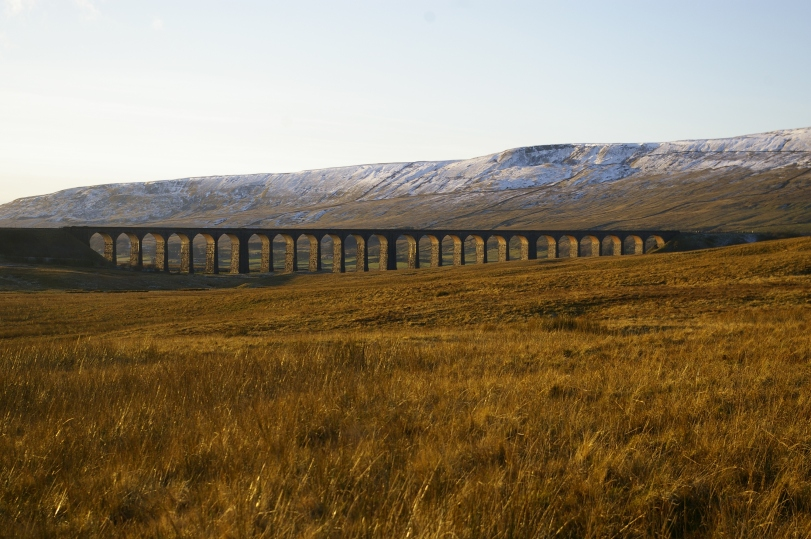 Ribblehead Viaduct with Whernside topped in snow in the background.